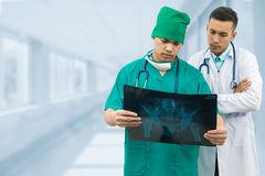 Surgeon and doctor looking at x-ray film. Doctor and surgeon examining xray film, diagnose patient `s waist bone injury. Surgery operation and medical concept Royalty Free Stock Photos