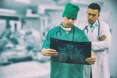 Surgeon and doctor looking at x-ray film. Doctor and surgeon examining xray film, diagnose patient `s waist bone injury. Surgery operation and medical concept Stock Image