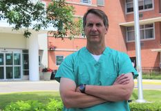 Surgeon or Doctor or Physician or Clinician Stands Outside Hospital with Arms Crossed Stock Photos