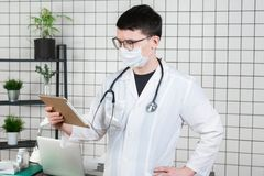 Surgeon doctor with tablet computer in hospital office. Medical healthcare staff and doctor service stock image