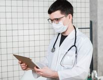 Surgeon doctor with tablet computer in hospital office. Medical healthcare staff and doctor service royalty free stock image