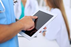 Surgeon doctor using tablet computer, close-up of hands at touch pad screen Royalty Free Stock Photography