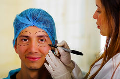 Surgeon drawing marks on male face. Plastic surgery concept.  stock photography