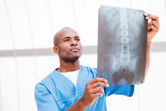 Surgeon examining X-ray image. Confident young African doctor in blue uniform examining x-ray Royalty Free Stock Image