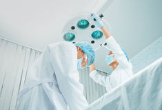 Surgeon and female assistant working in operating room. Serious men surgeon and female assistant working in operating room, teamwork. Focus on men surgeon Stock Image