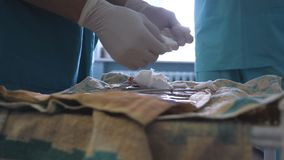 Surgeon in gloves preparing instruments before surgery. Doctor is preparing the tools for surgery. Close up stock footage