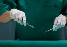 Surgeon in green uniform. Holding surgical tools Royalty Free Stock Photos