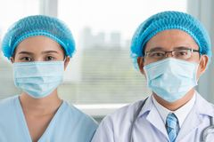 Surgeon and his female assistant Stock Photo