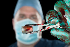 Surgeon holding bullet Stock Photo