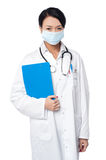 Surgeon holding clipboard. Face covered with surgical mask Stock Images