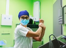 Surgeon in the hospital washing hands. Female Surgeon in a medical mask and in a suit in the hospital washing thoroughly her hands before performing a surgery royalty free stock images
