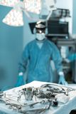 Surgeon looking at camera in operating room with tools. On foreground Stock Photos