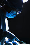 Surgeon looking down, concentrating, and holding surgical equipment in the operating room Stock Photo