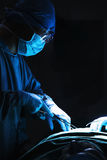 Surgeon looking down, working, and holding surgical equipment with patient lying on the operating table Stock Image