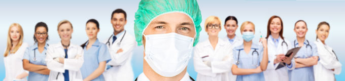 Surgeon in medical cap and mask over team Royalty Free Stock Photos