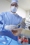 Surgeon In Operating Room. Male surgeon making preparation before a surgery in operating room Stock Image