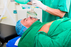 Surgeon in operating room with anesthetic mask Stock Photo
