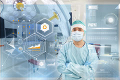 Surgeon in operating room at hospital with charts. Surgery, medicine, healthcare and people concept - surgeon in mask operating room at hospital with virtual Royalty Free Stock Image
