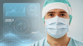 Surgeon in operating room at hospital. Surgery, healthcare, medicine and people concept - surgeon in mask with diagram and virtual screen projection Royalty Free Stock Photos