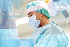 Surgeon in operating room at hospital. Surgery, healthcare, medicine and people concept - surgeon at operation in operating room at hospital with diagram and Royalty Free Stock Image