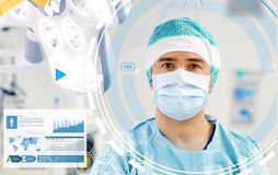 Surgeon in operating room at hospital. Surgery, medicine and people concept - surgeon in mask operating room at hospital Stock Images