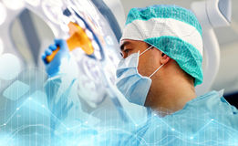 Surgeon in operating room at hospital. Surgery, medicine and people concept - surgeon in mask adjusting lamp in operating room at hospital Stock Photos