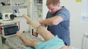 Surgeon puts on compression stocking on patient leg after operation of sclerotherapy. Concept of vascular surgery stock footage