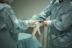 Surgeon putting on gloves Royalty Free Stock Images