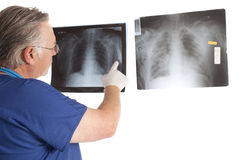 Surgeon and x-rays. Surgeon studying x-rays to develop a diagnosis for aptients condition Stock Image