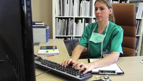 Surgeon reviewing patient data and typing medical report stock video footage