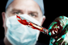 Surgeon with scalpel. A male surgeon holds up a sharp, bloody scalpel during surgery Stock Image