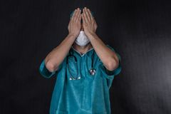 Surgeon in scrubs covering eyes. Stock Photos