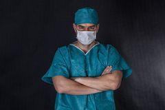 Surgeon in scrubs with hands folded. Stock Photo