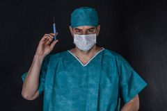Surgeon in scrubs holding syringe. On a black background Stock Photo