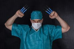 Surgeon in scrubs with syringes claws Royalty Free Stock Photo
