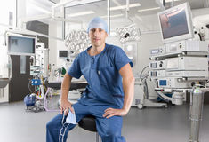 Surgeon sitting on stool in hospital operating room Royalty Free Stock Photography
