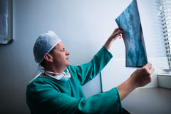 Surgeon sitting at window and checking x-ray Stock Images