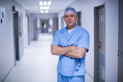 Surgeon standing with arms crossed in hospital corridor. Portrait of surgeon standing with arms crossed in hospital corridor Royalty Free Stock Photos