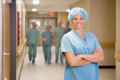 Surgeon Standing Arms Crossed In Hospital Corridor. Portrait of happy female surgeon standing arms crossed with team walking in hospital corridor Royalty Free Stock Photography