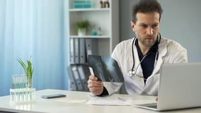 Surgeon studying x-ray of bone and making prescription in online card on laptop royalty free stock image