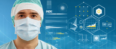 Surgeon in surgical mask and hat over charts. Surgery, medicine, healthcare and people concept - surgeon in surgical mask and hat over blue background and Stock Photography