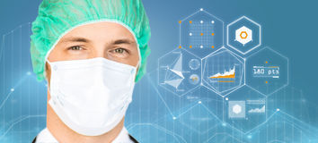Surgeon in surgical mask and hat over charts. Surgery, medicine, healthcare and people concept - surgeon in surgical mask and hat over blue background and Royalty Free Stock Photography