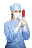 Surgeon with the syringe. Female doctor in a surgical suit holding a syringe Stock Photography