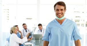 Surgeon taking off mask with staff talking behind him