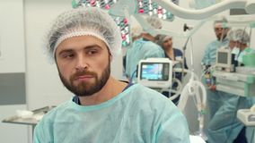 Surgeon thinks about some problem. Bearded surgeon thinking about some problem at the surgery room. Close up of male medical worker having sad face. Middle aged Stock Photo
