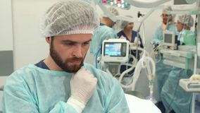 Surgeon touches his beard. Middle aged surgeon touching his beard at the operating room. Caucasian medical specialist in steril gloves thoughtfully looking down Royalty Free Stock Photo