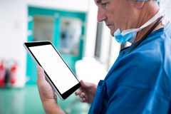 Surgeon using digital tablet in corridor. Surgeon using digital tablet in hospital corridor Royalty Free Stock Photo