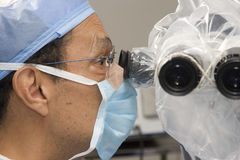 Surgeon Using Operating Microscope Stock Images