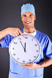 Surgeon with wall clock Royalty Free Stock Image