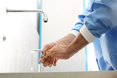 Surgeon washing hands. The doctor washes his hands, disinfect their hands before surgery royalty free stock image